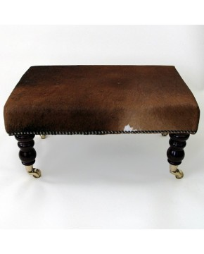 Small plain brown cowhide footstools with turned mahogany legs and brass castors